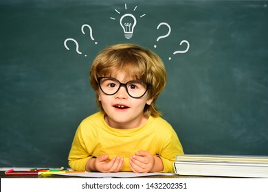 Little student boy happy with an excellent mark. Cute little preschool kid boy in a classroom. Cute boy with happy face expression near desk with school supplies