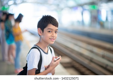 Little student boy waiting for train on platform with mobile in hands
