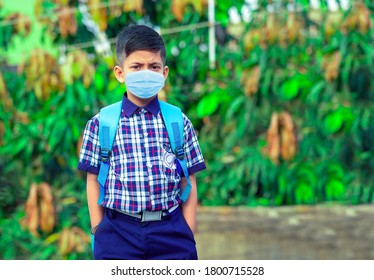 Little student boy wearing school uniform and face mask going to school with bag pack in corona virus pandemic.
