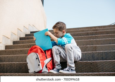 Little student getting ready for a lesson. Young school boy sitting outside a school and taking a book out of a bag.