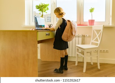 Little student girl of 8 years old in school uniform with a backpack uses laptop. School, education, knowledge and children