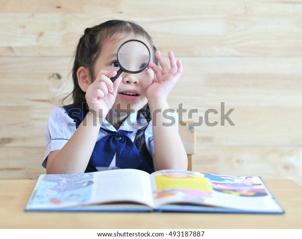 little student girl looking through a magnifying with smile face
