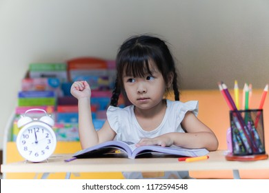 Little student girl reading a book or doing homework at home .The decision of lessons. education and school concept.
