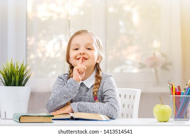 Little student girl sitting at the table and reading a book. The child shows a sign shh. The concept of education and school. In the background - the light from the window.