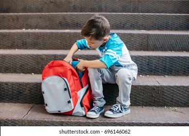 Little student on his first day of school checking books inside his backpack