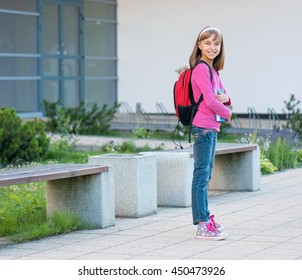 Little students with books - full length outdoor portrait. Beginning of class after vacation. Back to school concept.