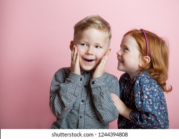 Little stylish girl and boy whispering secret to the ear. surprised interesting gossip. funny kids isolated on ping background.