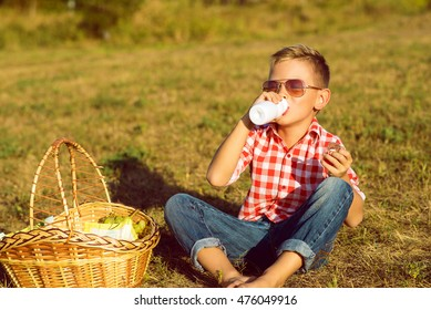 Little stylish kid in sunglasses is sitting near the basket with grapes on the meadow drinking yogurt. Dairy products concept. Close up. Outdoor shot. Copy-space