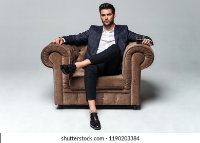 Little stylish rest. Full length of handsome young man looking at camera while sitting against white background in big chair