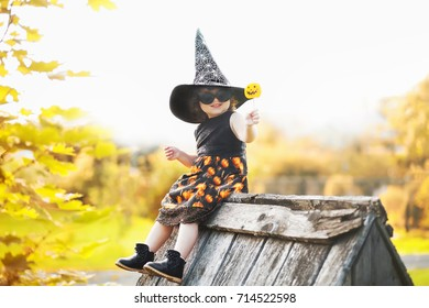 Little stylish witch outdoors, wearing halloween costume and sunglasses, ready for trick-or-treat, sitting on a roof of her little wooden house