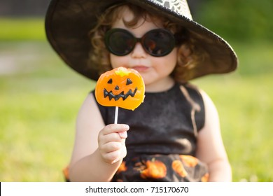 Little stylish witch outdoors, wearing halloween costume, ready for trick-or-treat