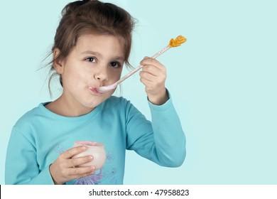 little successful laughing girl eating yogurt