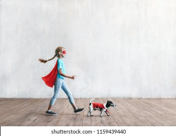 Little superhero with a dog in the studio