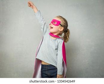 Little superhero wearing mask and cloak