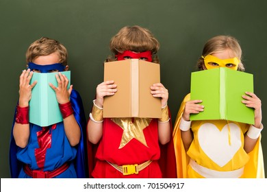 little superheroes in costumes holding books, chalkboard behind