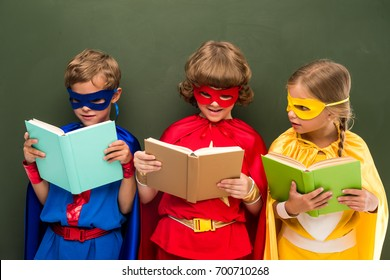 little superheroes in costumes reading books, chalkboard behind