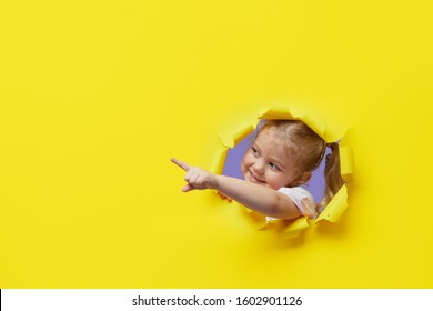 Little surprised child looking, peeping through the bright yellow paper hole. Showing hand to side. Advertise childrens goods. Copy space for text