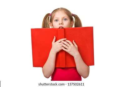A little surprised girl with a book looking at camera. Isolated on white background