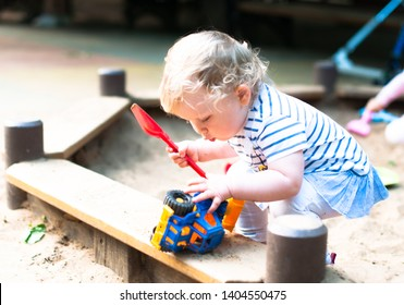 A little sweet baby playing in the sandbox in the sunny spring day