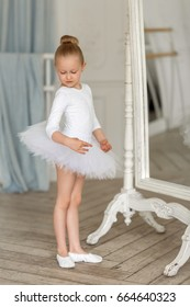 A little sweet ballerina in a white tutu stands by the mirror and admires herself. The Ballet.