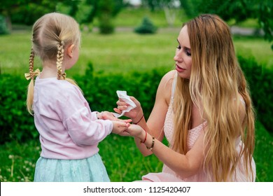 little and sweet blonde girl in a cute gray dress together with toothy smile beautiful mother wipe hands with wet wipes in the park against the background of trees and greenery