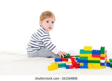 Little sweet boy plays with children blocks set on a white background. Early development and learning toys.