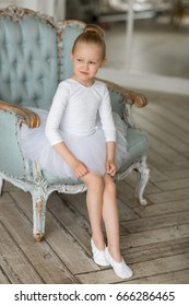 Little sweet girl ballerina in a white tutu and kitschka sitting on a blue chic chair. Concept of children and dance.