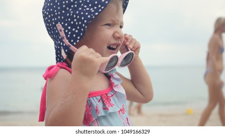 A little sweet girl in a choca in polka dots, playing with children's sunglasses. 1920x1080. full hd