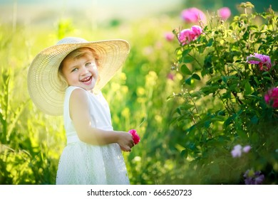 Little sweet girl in her mother's hat in the garden of a tea rose