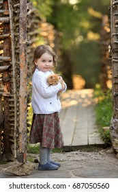 A little sweet girl in a white sweater and a dress holding a red-haired little kitten standing by the wicker of a village fence
