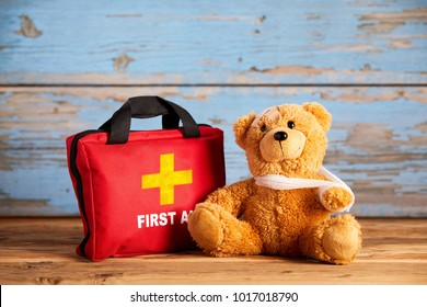 Little teddy bear with an injured arm in a sling sitting alongside a red First Aid bag on rustic wood in a concept of paediatric healthcare and emergency triage