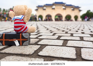 Little teddy bear with nostalgic sailer suit sitting on suitcase, lift his arms up to say hooray in Taipei city, Taiwan/ Cutie Happy to Travel in Taipei