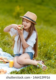 little teen girl eats sandwich at a picnic in nature with pleasure. child in white blouse eating sandwich sitting on the grass in the forest.