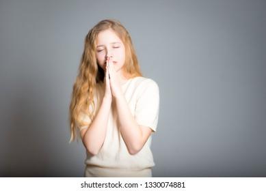 little teen girl prays, studio photo over background
