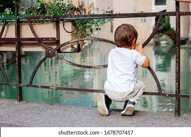 Little thoughtful sad boy looking from the bridge at Thiou River in Annecy, France squat on haunches. Child in the city. Little tourist. Discovering Europe, traveling with kid. People from behind