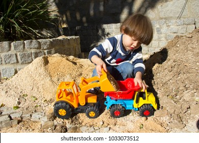 little three year old boy playing in the sand with a digger and dump truck.