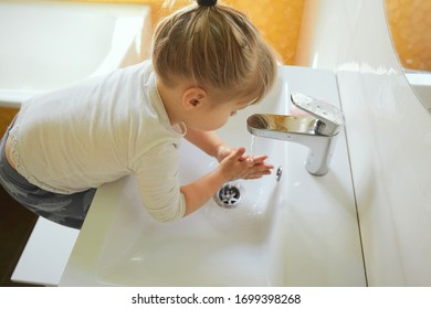 Little three years girl wearing white shirt washing hands in bathroom