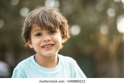 little three years old boy portraits in summer afternoon smiling