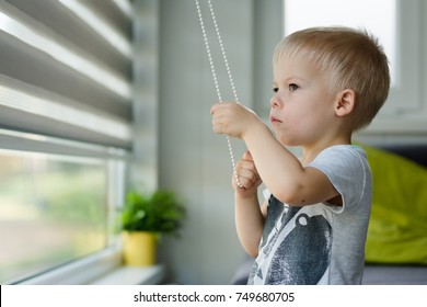 Little, three years old boy he raises the blinds in the windows and looking out  the window