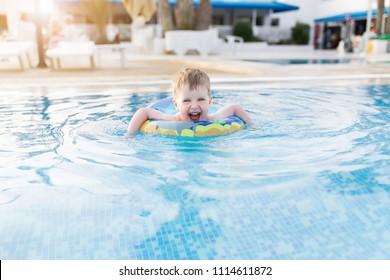 Little three years old kid boy swimming and splashing in swimming pool in swimming circle. Smiling and laughing Toddler having fun at summer vacation, leisure activity