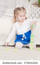 a little three-year-old girl plays cubes on which letters and numbers are drawn, on the floor near the bed