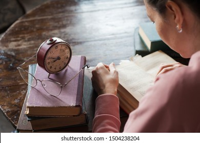 Too little time. An alarm clock stands on a stack of books, next to glasses, on a table in an old library, in front of a girl bent over a book. Stress during exams. Top view and over the shoulder.