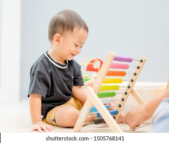 Little toddler asian cute handsome boy using the abacus with colorful beads to learn how to count at home.Portrait of little toddler boy with mother using abacus.Brain, Thinking, Child development.
