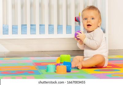 Little toddler baby boy sitting on children carpet near crib building pyramid of blocks looking at camera
