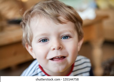 Little toddler boy with blue eyes and blond hair indoor