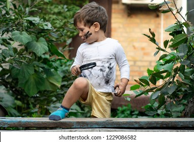 Little toddler boy with dirty face and dirty clothes looking through a magnifying glass on nature. Children playing outside with dirty hands.
