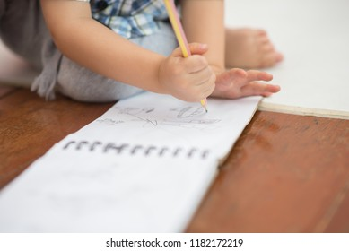 Little toddler boy draw pictures on a paper by use pencil