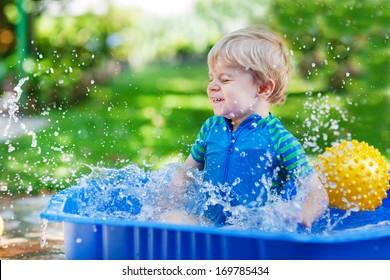 Little toddler boy having fun with splashing water in summer garden pool