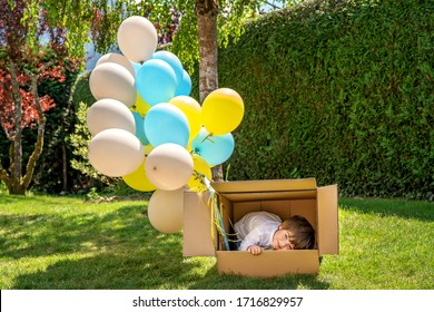 Little toddler boy hiding inside cardboard box with colorful air balloons looking with sly face daydreaming. Childhood dreams, creativity and imagination. Birthday party gift. Missing friends alone