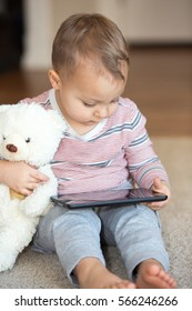 Little toddler boy holding a teddy bear while playing with computer tablet.